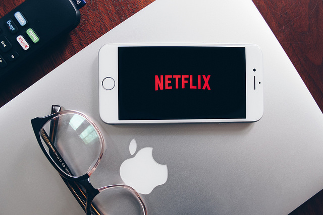 Image depicting a closed Apple laptop, with a pair of glasses and a smartphone resting on top. The phone is showing the Netflix logo.
