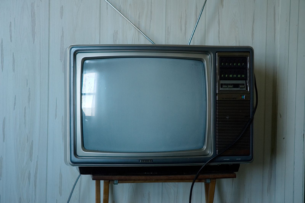 Image of an old fashioned television set. It is turned off, and light relfects against its blank grey screen.