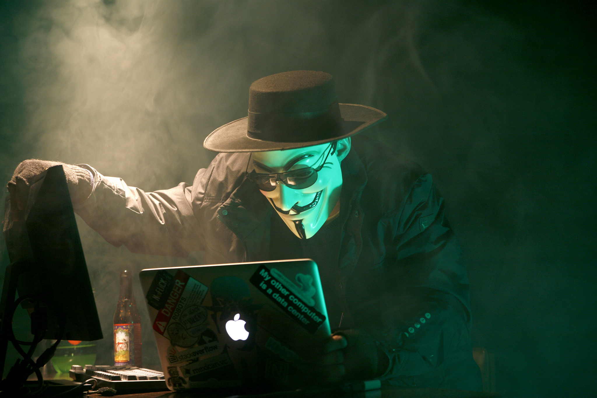 A person in a dark hat and trench coat peers down at two computer monitors. They are wearing a white mask, hiding their identity. The room is dark, and smoke floats in the air.