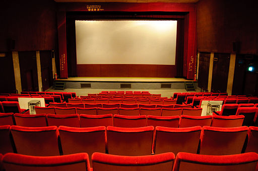 photograph shot from the back of an empty cinema, showing rows of bright red seats facing a blank screen