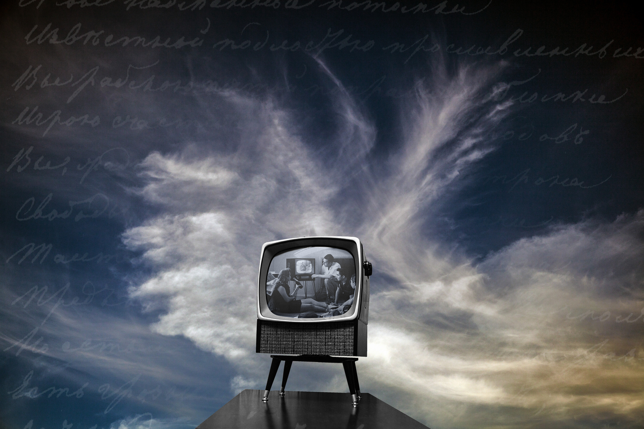 Photograph of an old-fashioned television set, up against the background of a cloudy sky. On the screen, a black and white image of a family watching television.