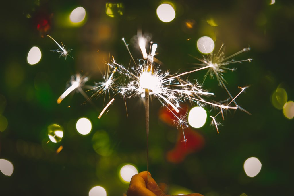 A close up image of a lit sparkler against a festive green background
