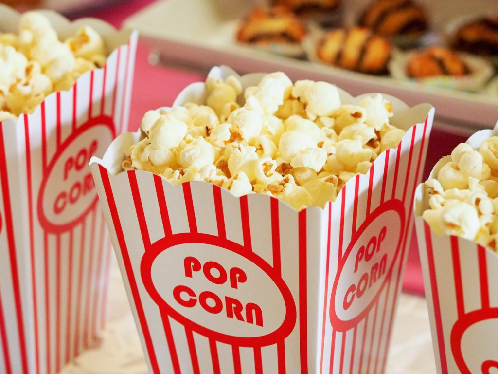 Photograph of fresh popcorn in a cheerful striped container