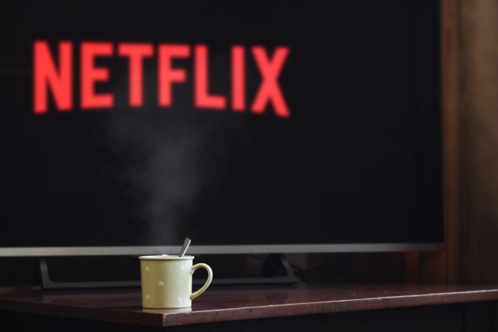 Photograph of a coffee mug sitting in front of a flat screen television showing the Netflix logo
