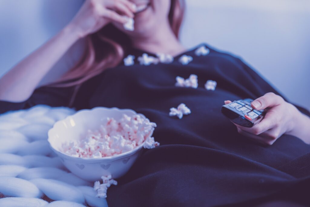 Image of a woman messily eating popcorn while watching television, holding a remote control in her hand.