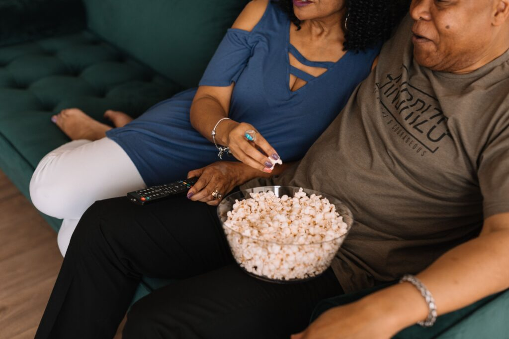 A man and woman sit snuggled on the couch watching television. She holds the tv remote and reaches into a bowl of popcorn sitting on his lap.