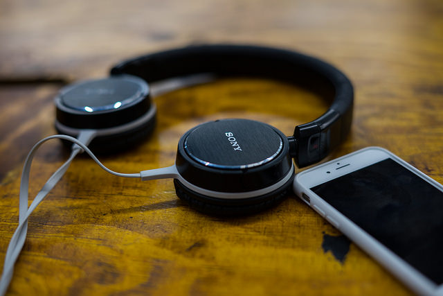 Photograph of black headphones lying flat on a wooden surface, close to a smartphone.