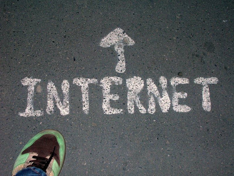"""Photograph of the word """"Internet"""" painted on a road in white paint. The photographer's green running shoe can be seen in the lower left corner. An arrow is painted on the ground, showing what direction to follow."""