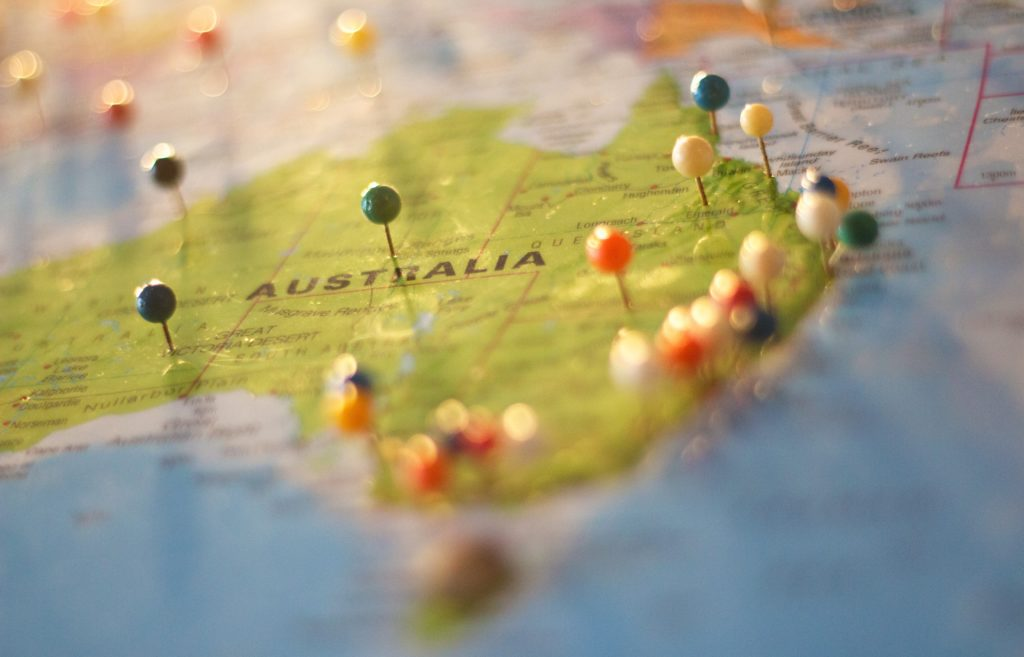 The image depicts a close up photograph of Australia on a map, with place names and state boundaries visible. Pins have been placed in various locations on the map, mainly down the East coast.