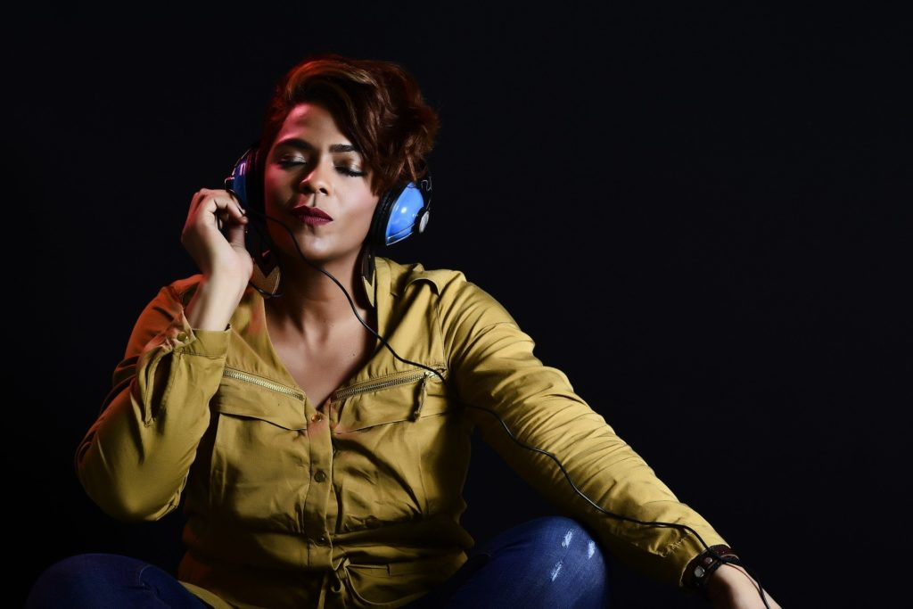 Photograph of a woman with a tranquil expression, her eyes closed, wearing blue headphones.