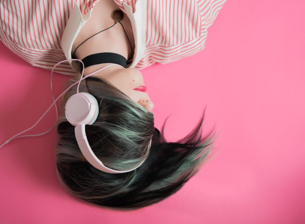 Photograph of a girl wearing pink lipstick, lying on the floor listening to headphones. Her dark hair swirles around her head, covering her eyes and the top of her head..
