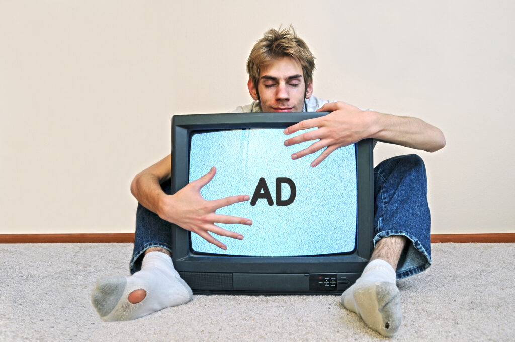 Photograph of a man hugging an old television set with the letters AD on the screen. His eyes are blissfully closed and his old socks have holes in them.